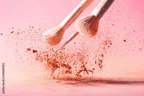 Plakaty różowe  make-up-brushes-with-powder-splashes-isolated-on-pink-background