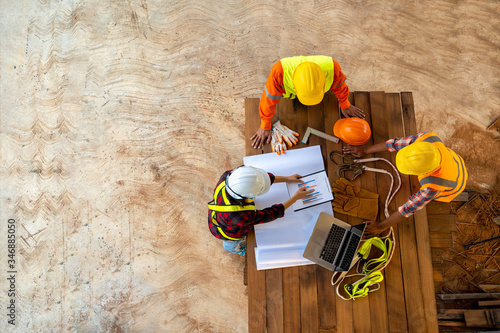 Obraz na płótnie Team of engineer and architects working, meeting, discussing,designing, planning, measuring layout of building blueprints at construction site,Top view,Construction concept
