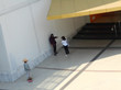High Angle View Of Woman Photographing Female Friend By Building