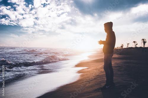 Photo persona mirando al mar en el atardecer