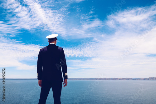 Photo Strong posture of a captain looking at the sea and faraway land on the horizon