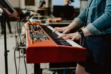 Closeup of a female playing on the red electric piano