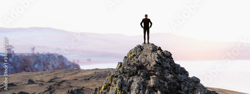 Fototapeta Vision concept, Successful businessman standing top peak mountain with sunset sky and looking forwards in panorama view, Successful and leader concept. obraz