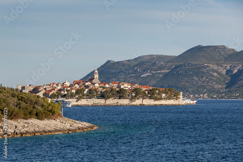 Fotografie, Obraz Defended medieval dalmatian town Korcula on the island of Korcula and mountains