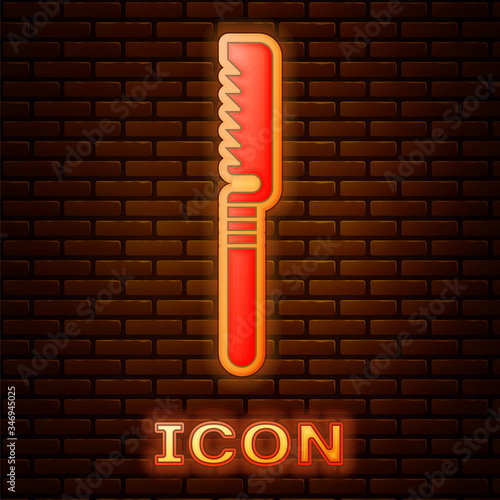 Photo Glowing neon Medical saw icon isolated on brick wall background