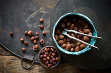 Old-fashioned Nutcracker And Bowls Of Hazelnuts