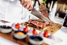 Hands Of Chef Slicing Tomahawk...