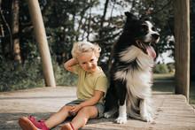 Netherlands, Schiermonnikoog, Girl With Border Collie Sitting On Boardwalk In The Forest