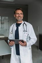 Portrait Of Smiling Doctor Holding Tablet