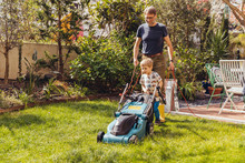 Father And Son Mowing The Lawn...