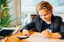 Smiling Boy Sitting At Desk With Workbook And Pocket Calculator