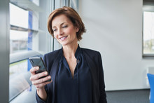 Businesswoman Using Cell Phone At The Window