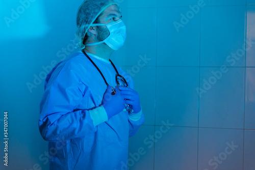 Un doctor  mostrando preocupación por resultados de un análisis o muestra de sangre en un test o jeringuilla tras el estrés vivido debido a la pandemia o virus, llamada Coronavirus o Covid-19 Wallpaper Mural