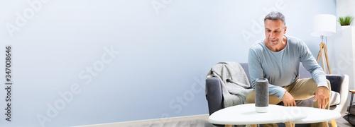 Man Listening To Wireless Speaker On Furniture