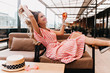 canvas print picture - Ecstatic blonde girl playing with her hair while chilling in cafe. Inspired young woman in striped dress enjoying champagne in restaurant in summer weekend.