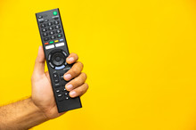 Close Up Male Hand Holding Television Remote Control On Isolated Yellow Background.