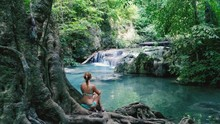 Rear View Of Woman Sitting In Front Of Lake At Erawan National Park