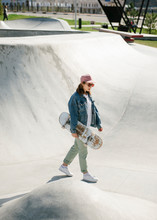 Young Woman Carrying Skateboard Looking Away Outdoor