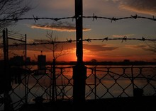 Silhouette Of Barbed Wire Fence At Sunset