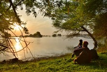 Friends Sitting On Grassy Field By Lake Against Sky During Sunrise