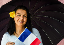 Woman With Umbrella Holds Flag Of France In Front Of Isolated Wall Background