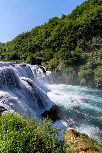 Scenic View Of Waterfall In Forest Against Clear Sky