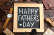 Leinwandbild Motiv Blackboard with words HAPPY FATHER'S DAY and male accessories on wooden background, flat lay