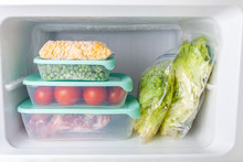 .Frozen Vegetables And Meat In Blue Plastic Containers. Frozen Yellow Corn, Green Peas, Red Tomatoes, Meat, Salad. Cold Freezer.