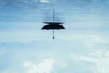 Upside Down Image Of Umbrella Floating On Sea Against Sky