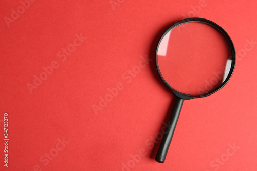 Canvas Print Top view of magnifying glass on red background, space for text