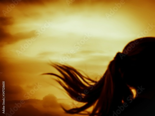 Fotografiet Rear View Of Woman Tossing Hair Against Scenic Sky