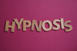 canvas print picture - Word HYPNOSIS made with wooden letters on magenta background, flat lay