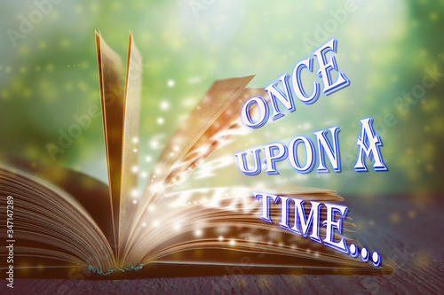 Fototapeta Open book of fairy tales with magic light and text Once upon a time obraz