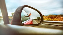 Woman Showing Middle Finger Reflecting On Side-view Mirror Of Car