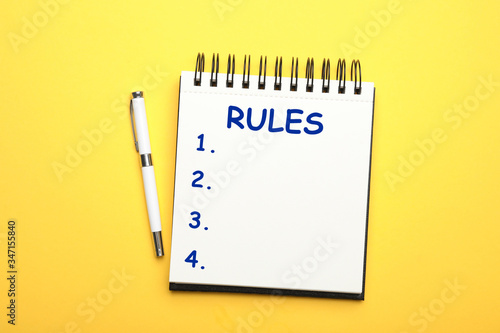 Fotografie, Obraz Notebook with list of rules and pen on yellow background, flat lay