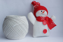 A Small Plush Snowman In A Red...