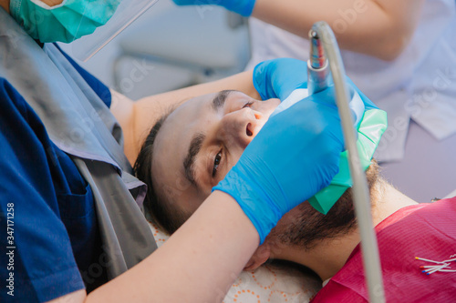 A dentist in blue gloves is drilling the teeth of a young guy in a dental office Wallpaper Mural