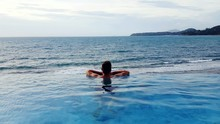 Rear View Of Man Swimming In Infinity Pool Against Sea