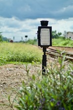 Railway Signal By Plants Against Cloudy Sky