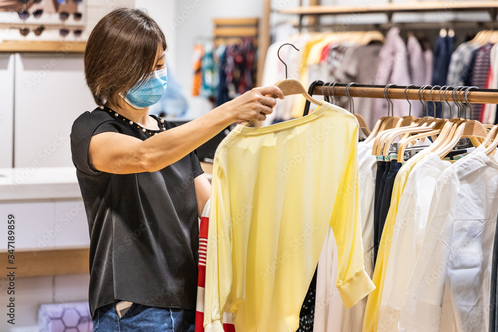 Fototapeta Asian woman shopping apparels in clothing boutique with protective face mask as new normal requirement