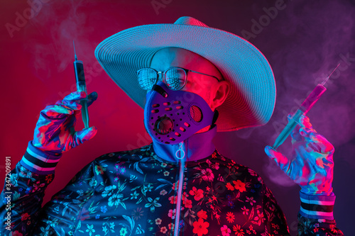 Strange man in medical respirator mask, glasses and hat holding two syrenges with coronavirus covid 19 test on red blue background Wallpaper Mural