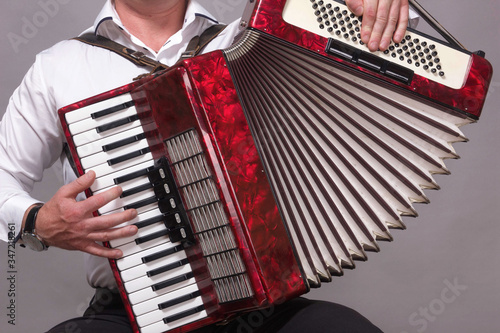 Closeup detail of hands playing a red accordion instrument Canvas-taulu