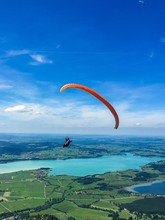 Person Paragliding Over Field Against Blue Sky