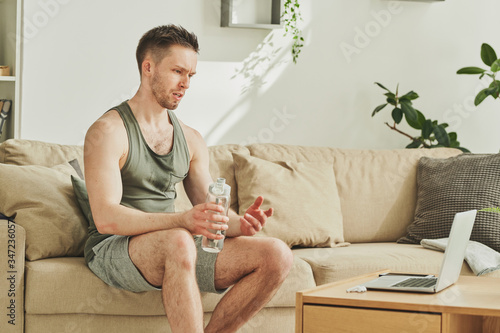 Young tired sportsman with bottle of water resting on couch after training Fototapet