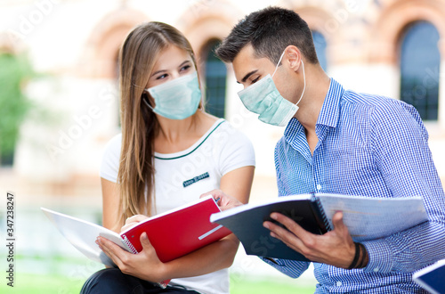 Fotografia Couple of students talking together wearing a mask - coronavirus concept