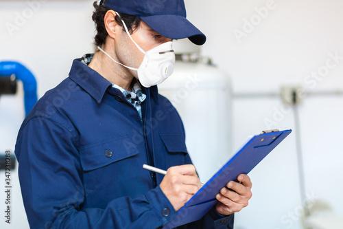 Fotografie, Obraz Plumber at work wearing a mask, coronavirus concept