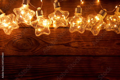 Fototapety, obrazy: Bright luminous Christmas garlands in the shape of stars lie on a dark wooden background.