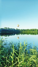 Hot Air Balloon Over Lake Against Clear Sky