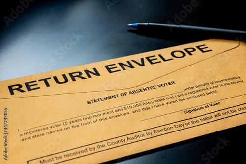 brown absentee ballot return envelope on a black desk with ink pen Wallpaper Mural