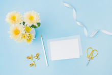 Mockup White Wedding Invitation And Envelope With Flowers In A Vase On A Blue Background